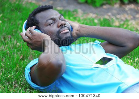 African American man listening music with headphones on green grass in park