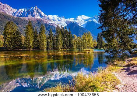 The snow-covered Alps and evergreen fir-trees  reflected in lake. Early fall in Chamonix, Haute-Savoie
