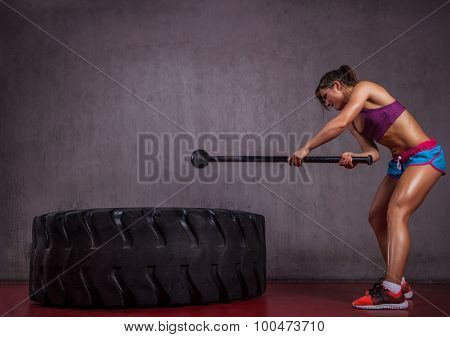 Girl with big tire and hammer.