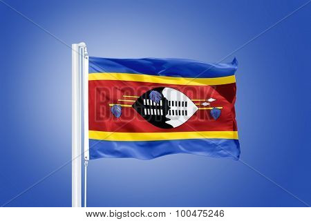 Flag of Swaziland flying against a blue sky.