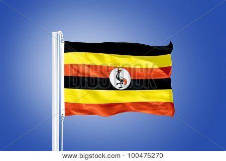 Flag of Uganda flying against a blue sky.