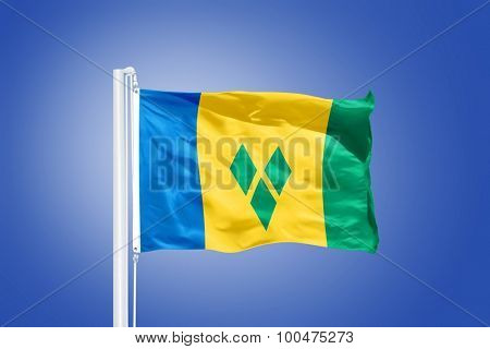 Flag of Saint Vincent and the Grenadines flying against a blue sky.