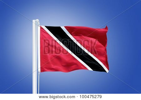 Flag of Trinidad and Tobago flying against a blue sky.