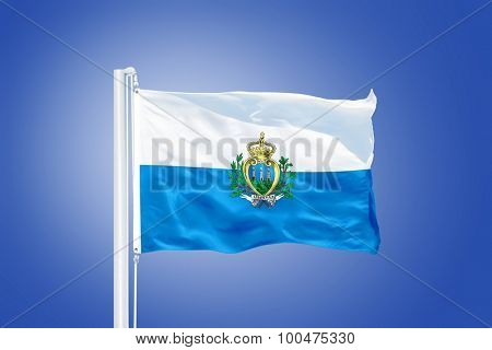 Flag of San Marino flying against a blue sky.
