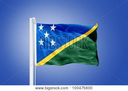 Flag of Solomon Islands flying against a blue sky.