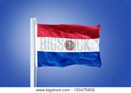 Flag of Paraguay flying against a blue sky.