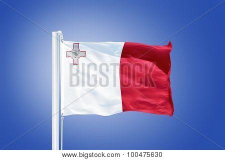 Flag of Malta flying against a blue sky.