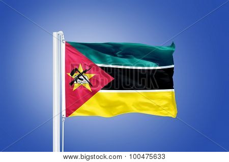 Flag of Mozambique flying against a blue sky.