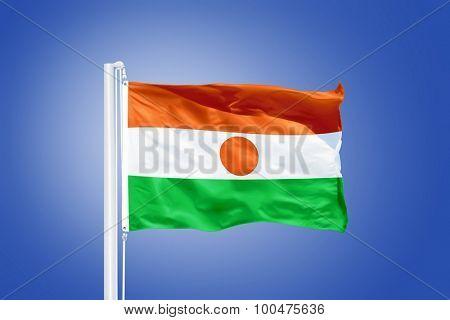 Flag of Niger flying against a blue sky.