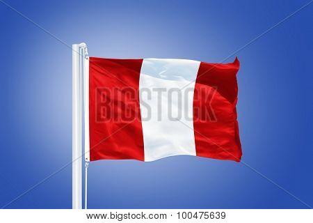 Flag of Peru flying against a blue sky.