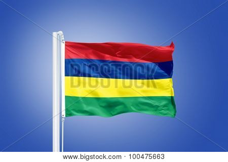 Flag of Mauritius flying against a blue sky.