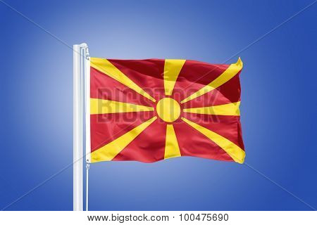 Flag of Macedonia flying against a blue sky.