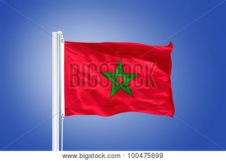 Flag of Morocco flying against a blue sky.