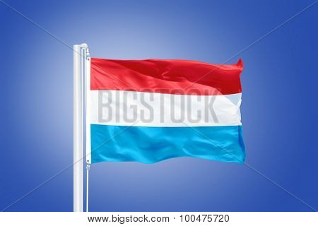 Flag of Luxembourg flying against a blue sky.