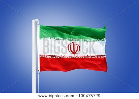 Flag of Iran flying against a blue sky.