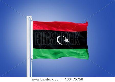 Flag of Libya flying against a blue sky.