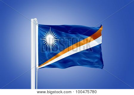 Flag of Marshall Islands flying against a blue sky.