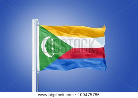 Flag of Comoros flying against a blue sky.