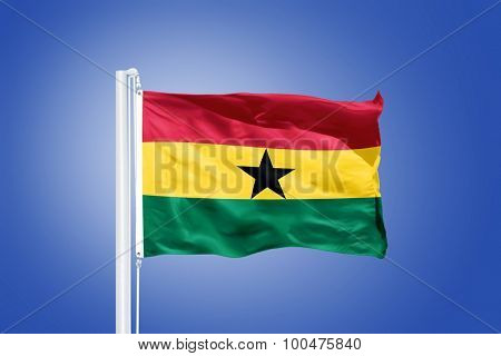 Flag of Ghana flying against a blue sky.