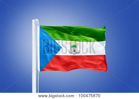 Flag of Equatorial Guinea flying against a blue sky.