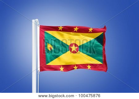 Flag of Grenada flying against a blue sky.