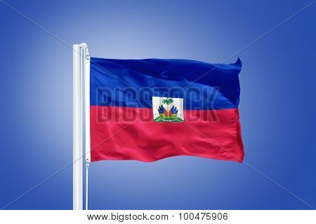 Flag of Haiti flying against a blue sky.
