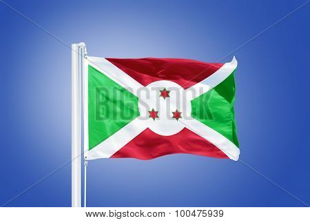 Flag of Burundi flying against a blue sky.