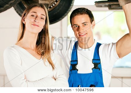 Mechanic repairing car of woman