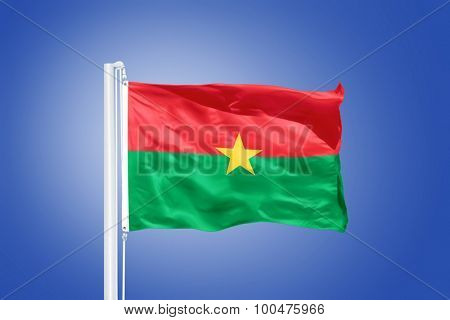 Flag of Burkina Faso flying against a blue sky.