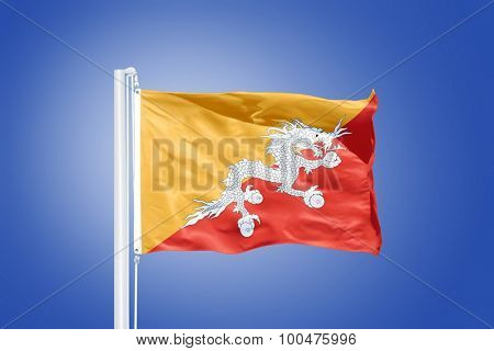 Flag of Bhutan flying against a blue sky.