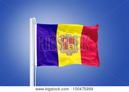 Flag of Andorra flying against a blue sky.