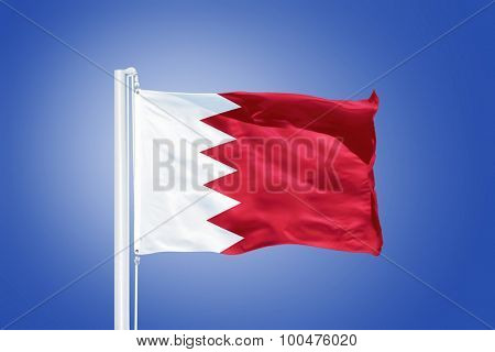 Flag of Bahrain flying against a blue sky.