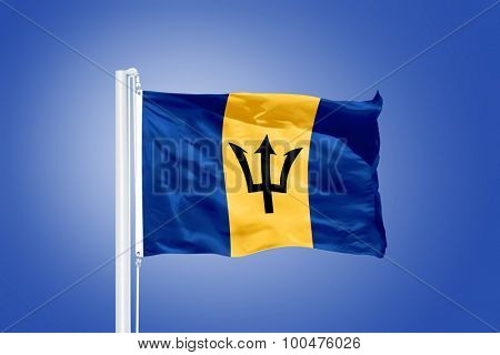 Flag of Barbados flying against a blue sky.