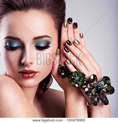 Beautiful woman face with green make-up and glass jewelry, creative nails