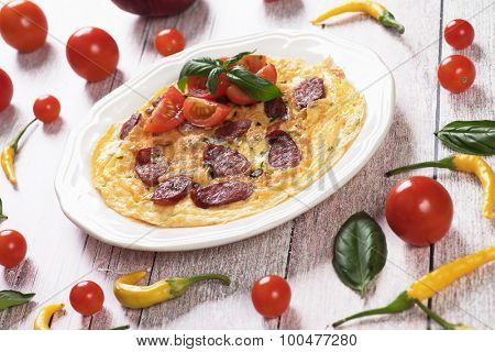 Omelet with pepperoni sausage, cherry tomato and basil served on a plate