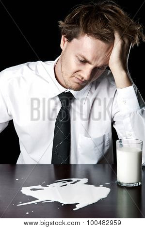 Businessman with spilled glass of milk, desaturated with black background