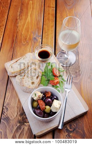 Platter with bread, olives, feta, side salad and a glass of wine