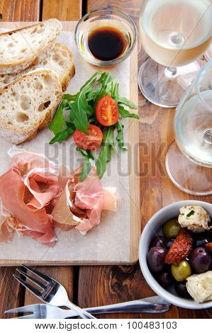 Serving of traditionally italian antipasto, prosciutto with bread and olives with wine