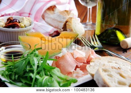 Gourmet platter of prosciutto, rocket and cantaloupe with bread and wine