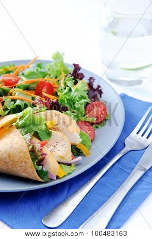 Colourful chicken wrap with plenty of fresh salad and a set of cutlery