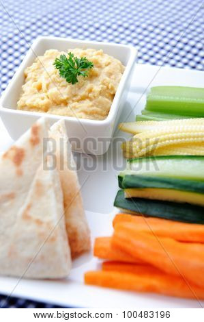 Vegetarian platter of raw carrots, corn, cucumber and celery sticks with chickpea dip and naan bread