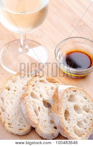 Slices of baguette with olive oil and balsamic vinegar, with a glass of wine