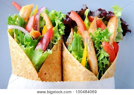 Delicious healthy meal consisting of a chicken burrito with plenty of fresh raw salad