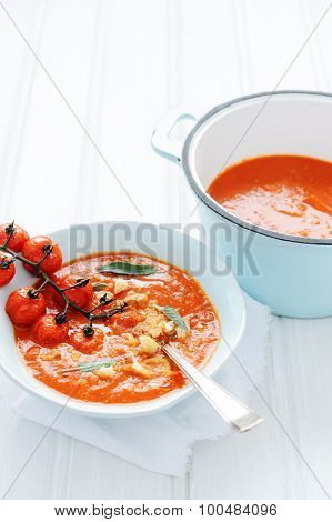 Vibrant red soup with oven roasted cherry tomatoes, croutons and sage