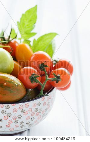 Close up tomatos in a bowl, cherry, roma, green, yellow, vine ripened with fresh green leaves