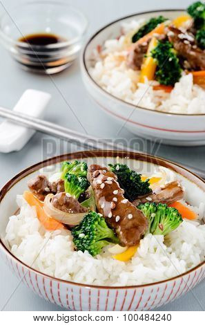 Close up on beef stir fry with vegetables on steamed white rice
