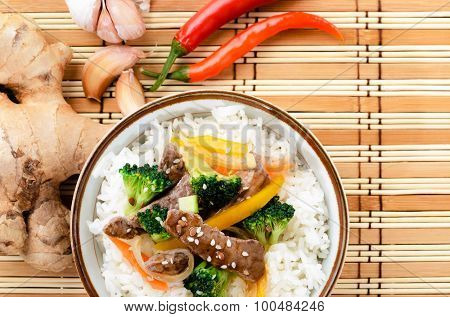 Chinese cuisine beef stir fry with vegetables on white rice, bamboo mat background with raw ingredients
