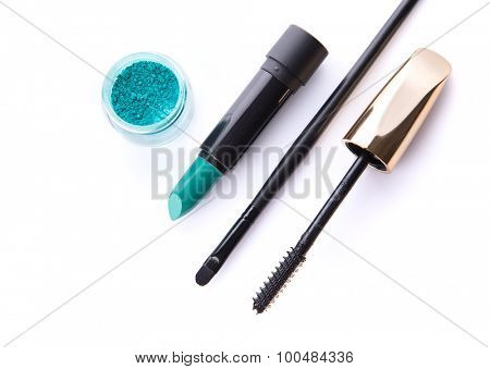 Top view of loose eye shadow, lipstick, makeup brush, and mascara, isolated on white background