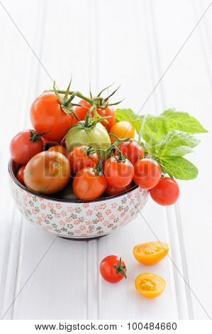 Arrangement of a variety tomatoes in a bowl, cherry, roma, green, yellow, vine ripened with fresh green leaves