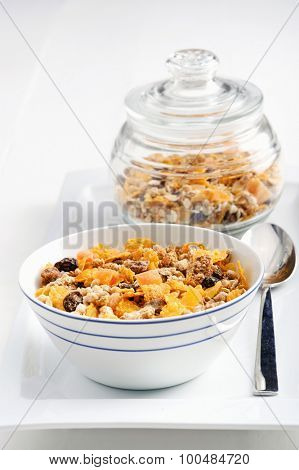 Serving of granola with jar in the background